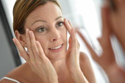 Woman applying facial cream on her face