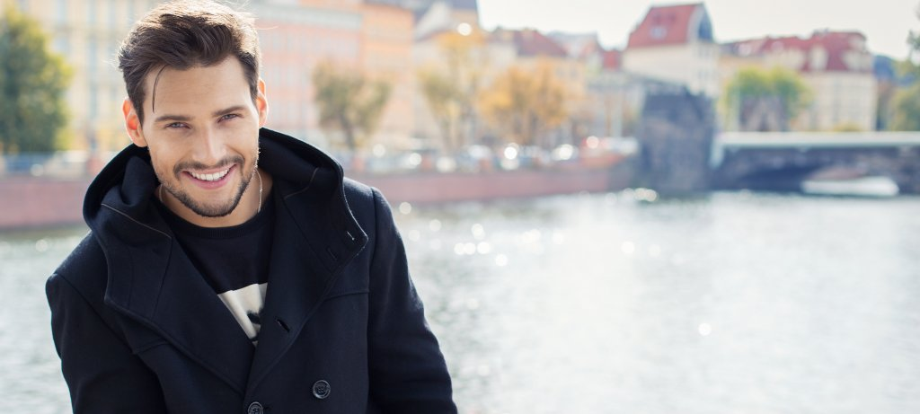 Paronamic photo with handsome smiling man in coat
