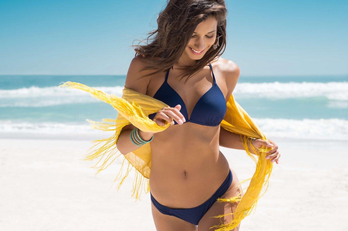 Woman with beach body running on beach