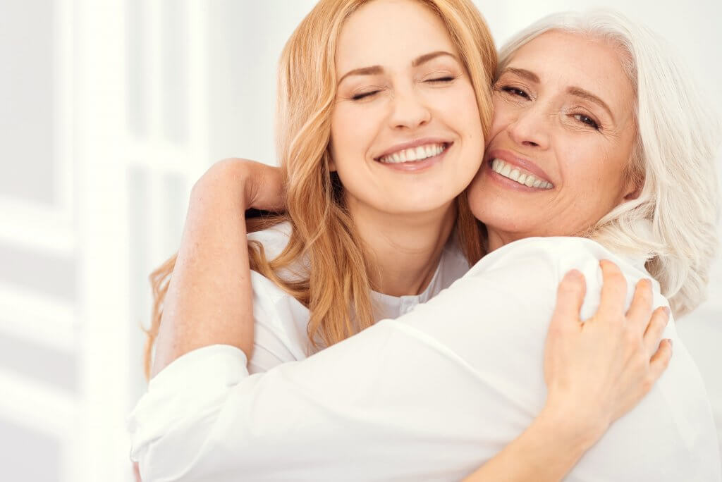 Radiant mother and daughter beaming, hugging