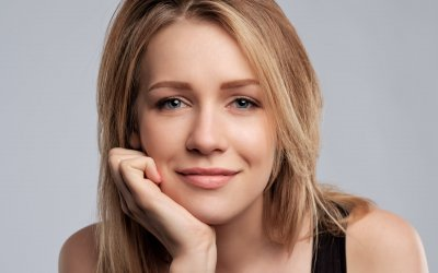 Beauty blonde woman with professionalperfect makeup. Looking with confidence at camera. Hand on chin
