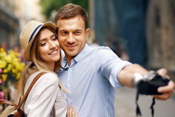 tourist-couple-taking-selfie-scaled.jpeg